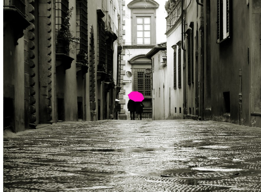 Wet street and two people with bright pink umbrella