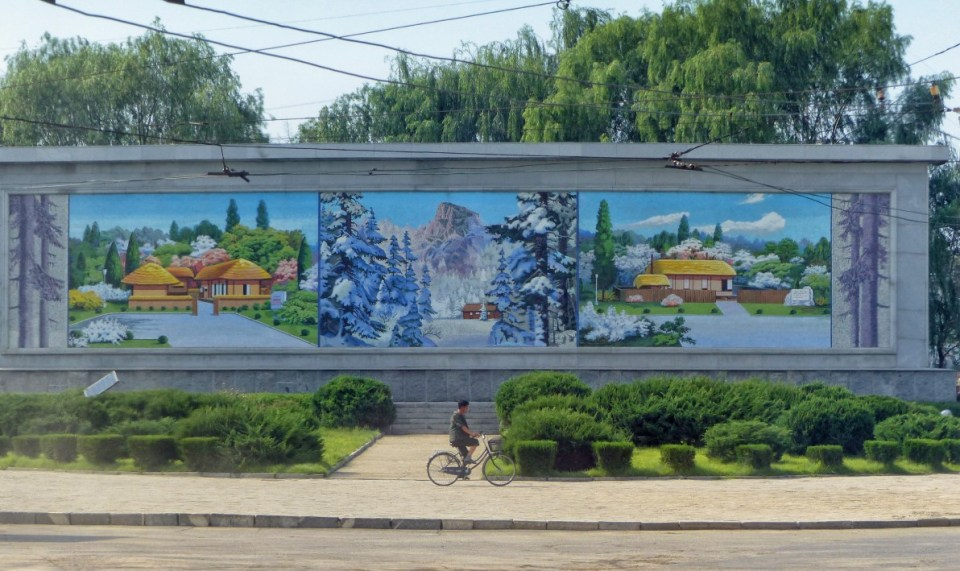 Man cycling past huge mosaic with rural scenes