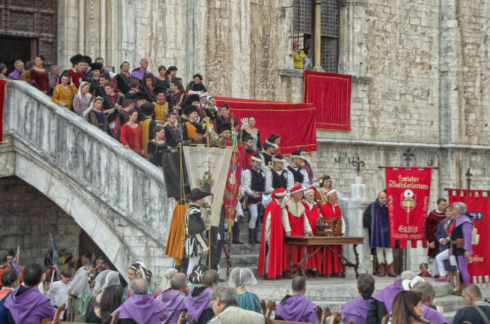 People in historical costume on steps with red banners