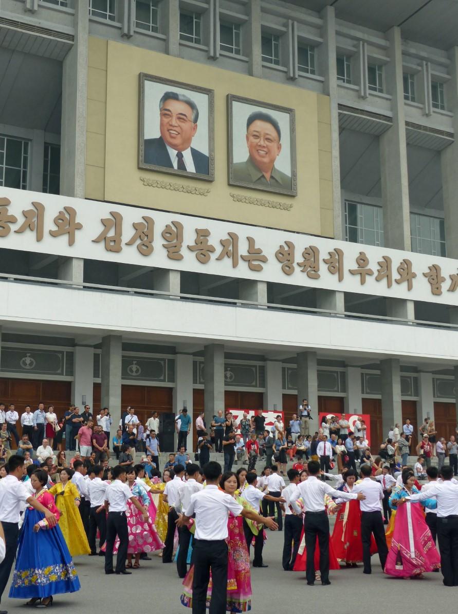 Women and men dancing in front of portraits of North Korean Leaders