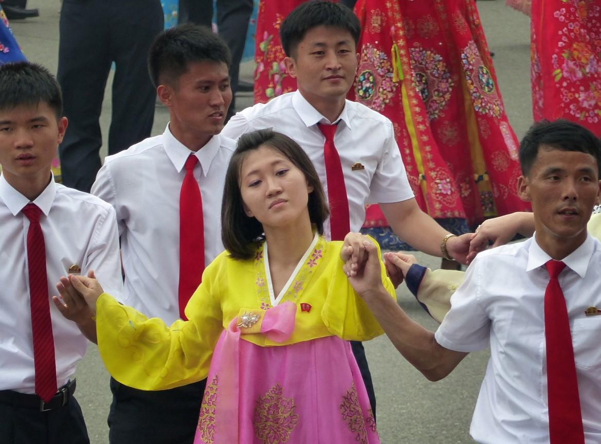Woman and men dancing in traditional Korean dress