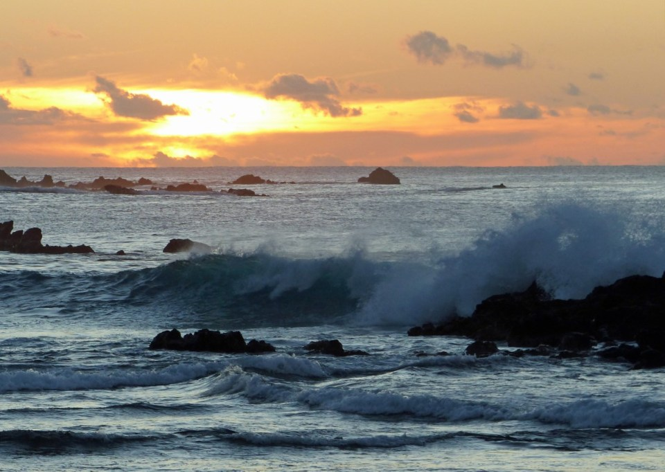 Sunset over the sea, waves breaking on rocks