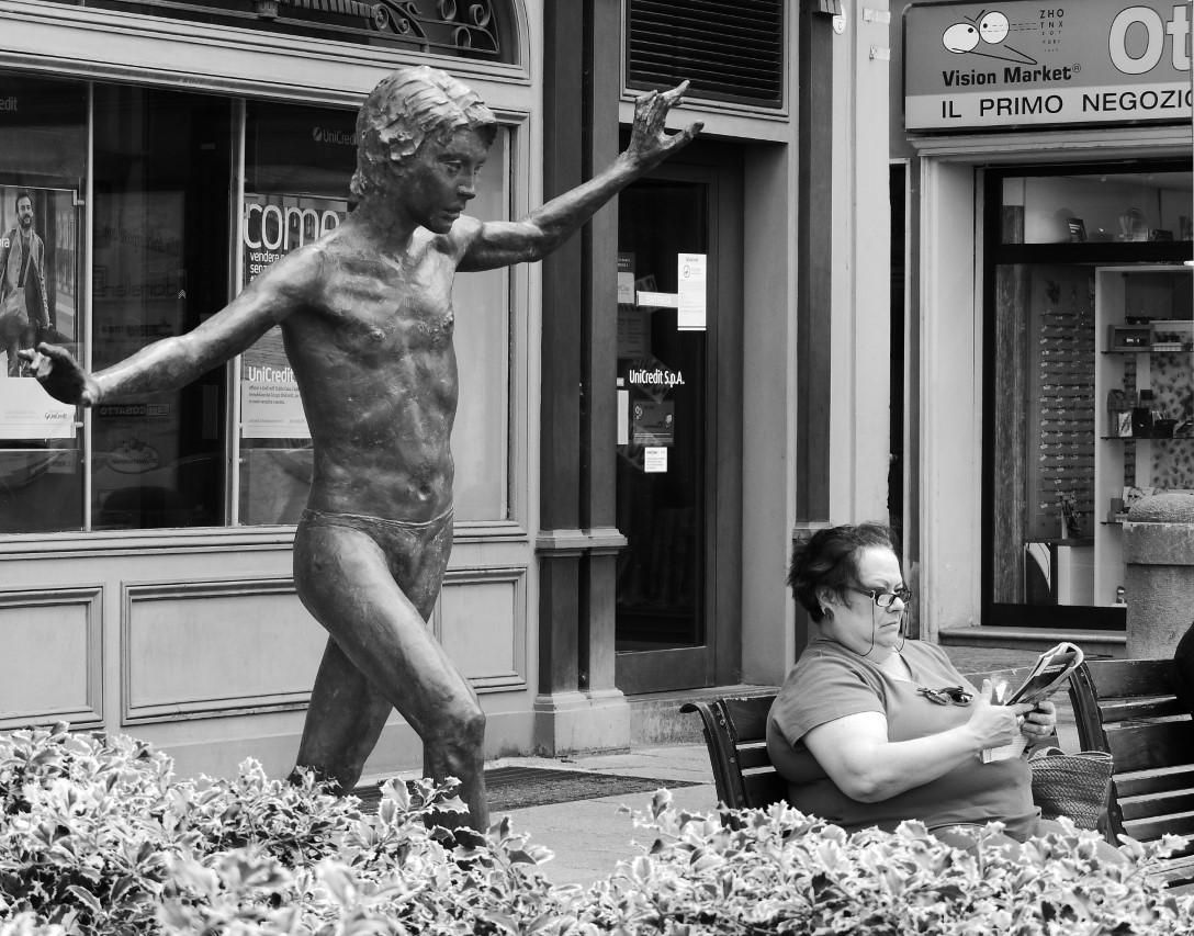 Woman reading a magazine next to a small statue