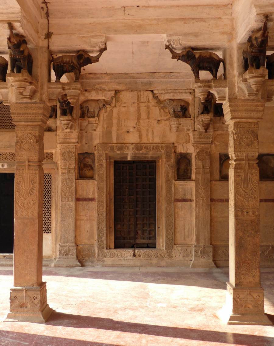 Room with stone pillars topped with carved elephants