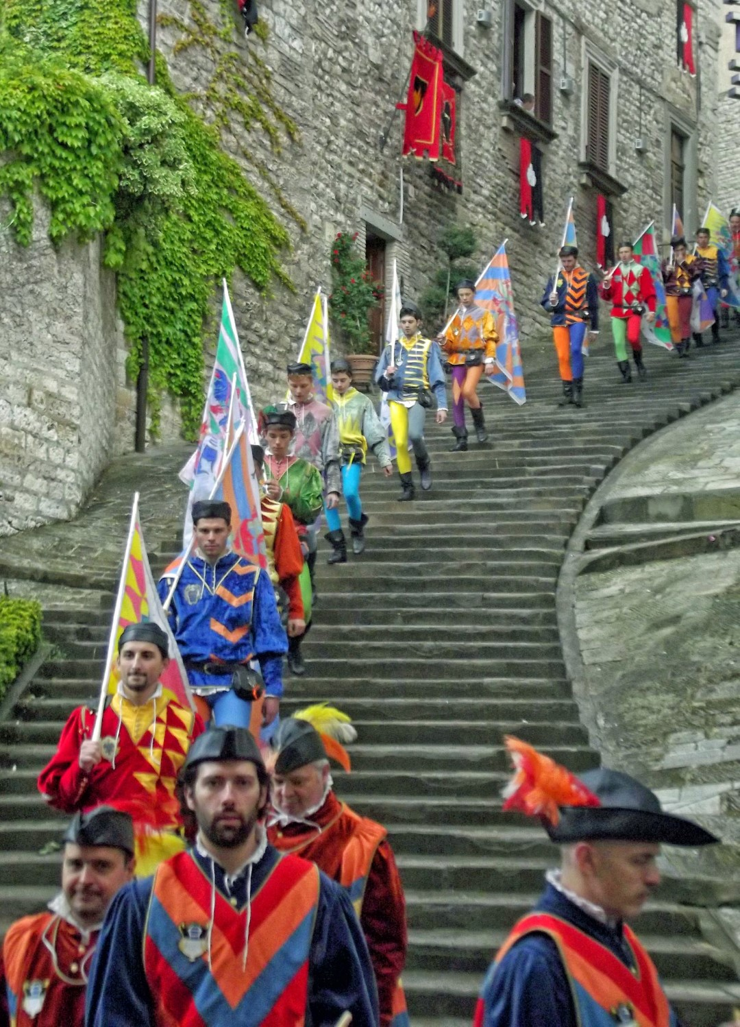 Men in colourful clothing on steps with flags