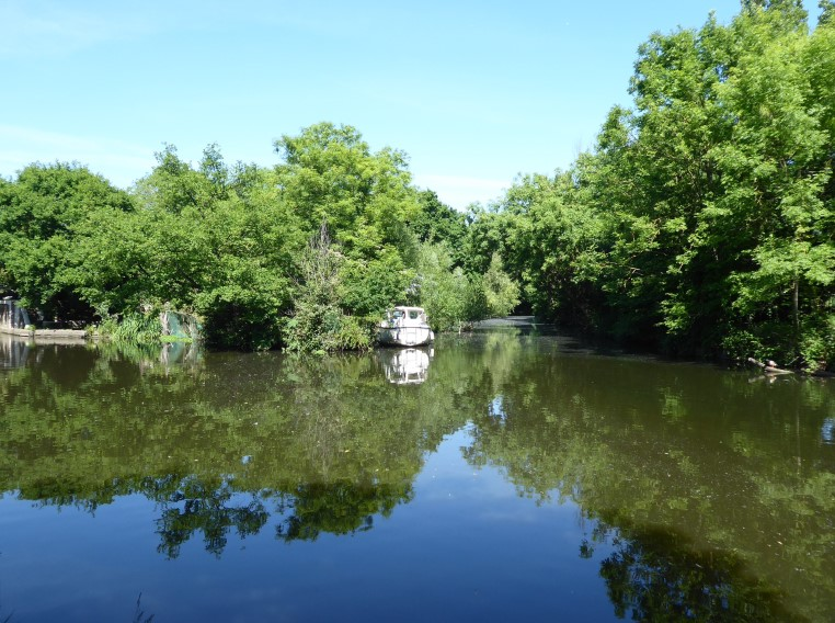 River with small white boat moored