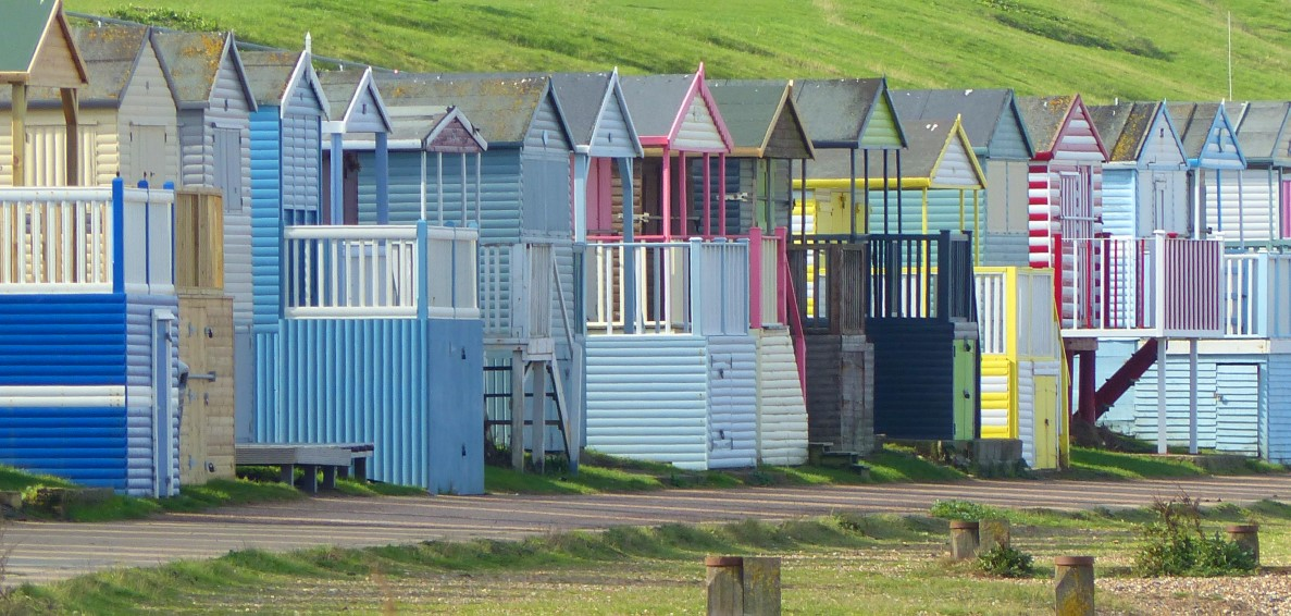 Row of wooden huts in pastel colours