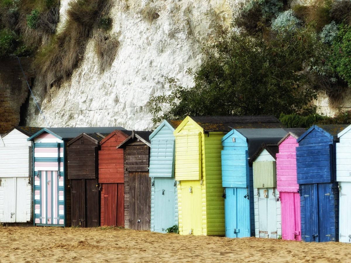 Row of coloured wooden huts on a beach