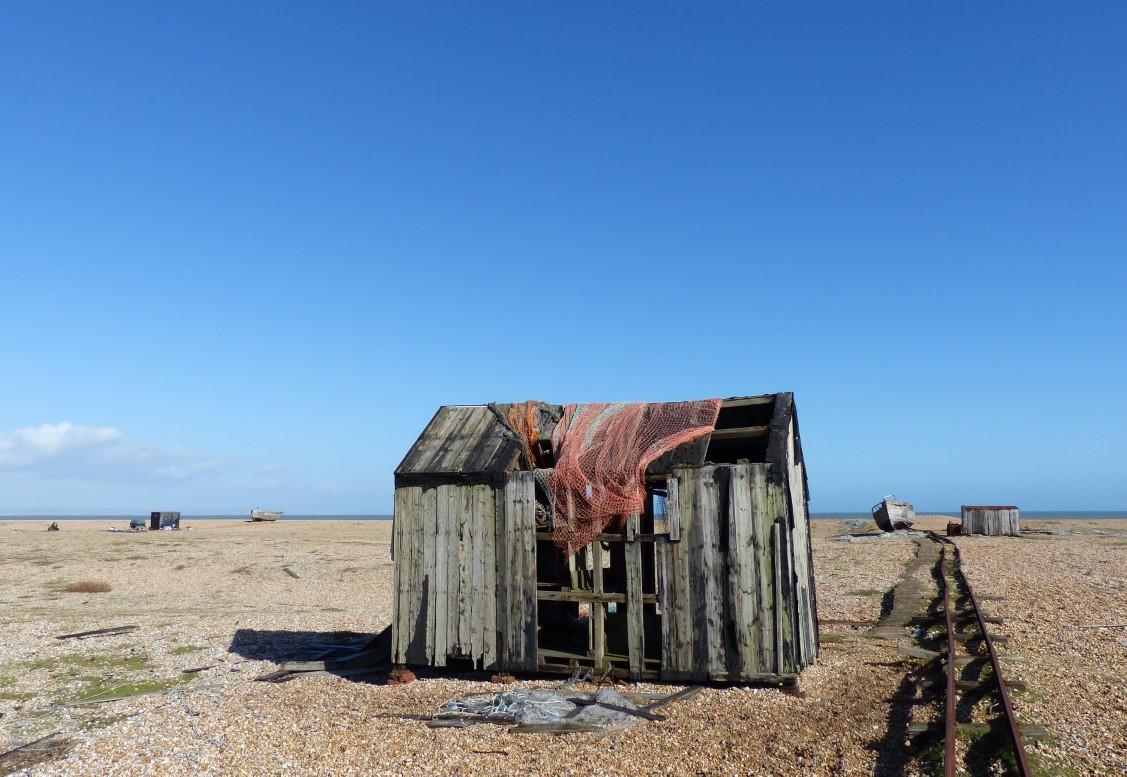 Old shed and rail track on a shingle beach
