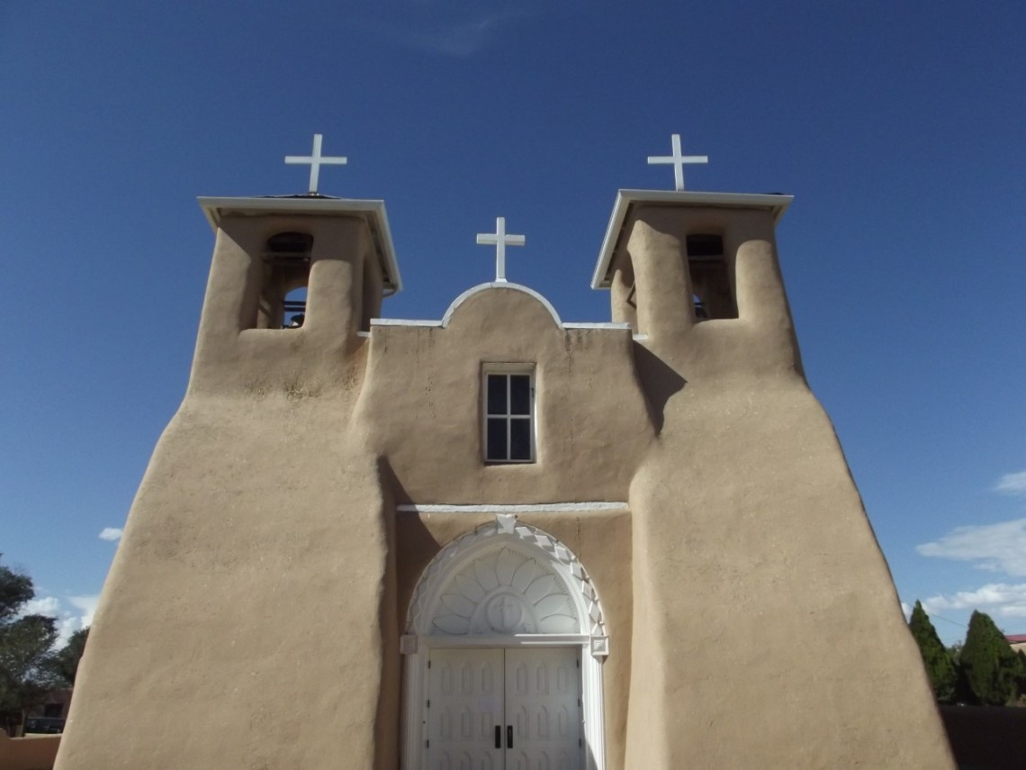 Large adobe church with white doors and crosses on towers