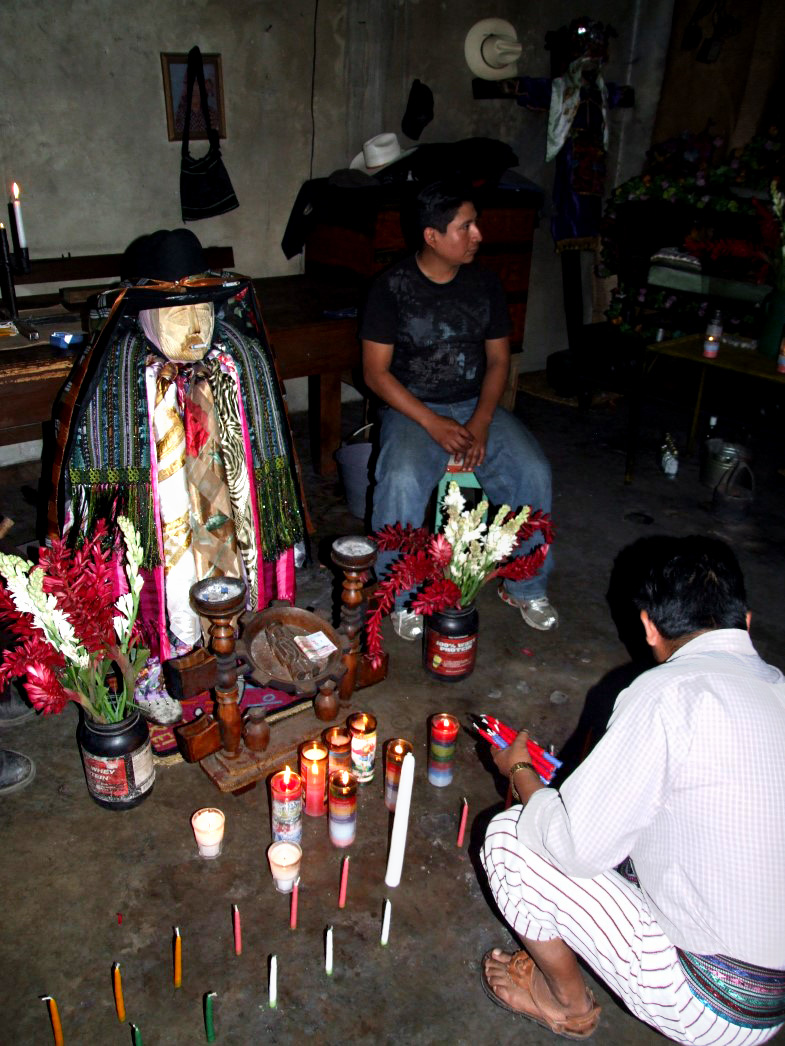 Clothed idol with candles and man leaving offering