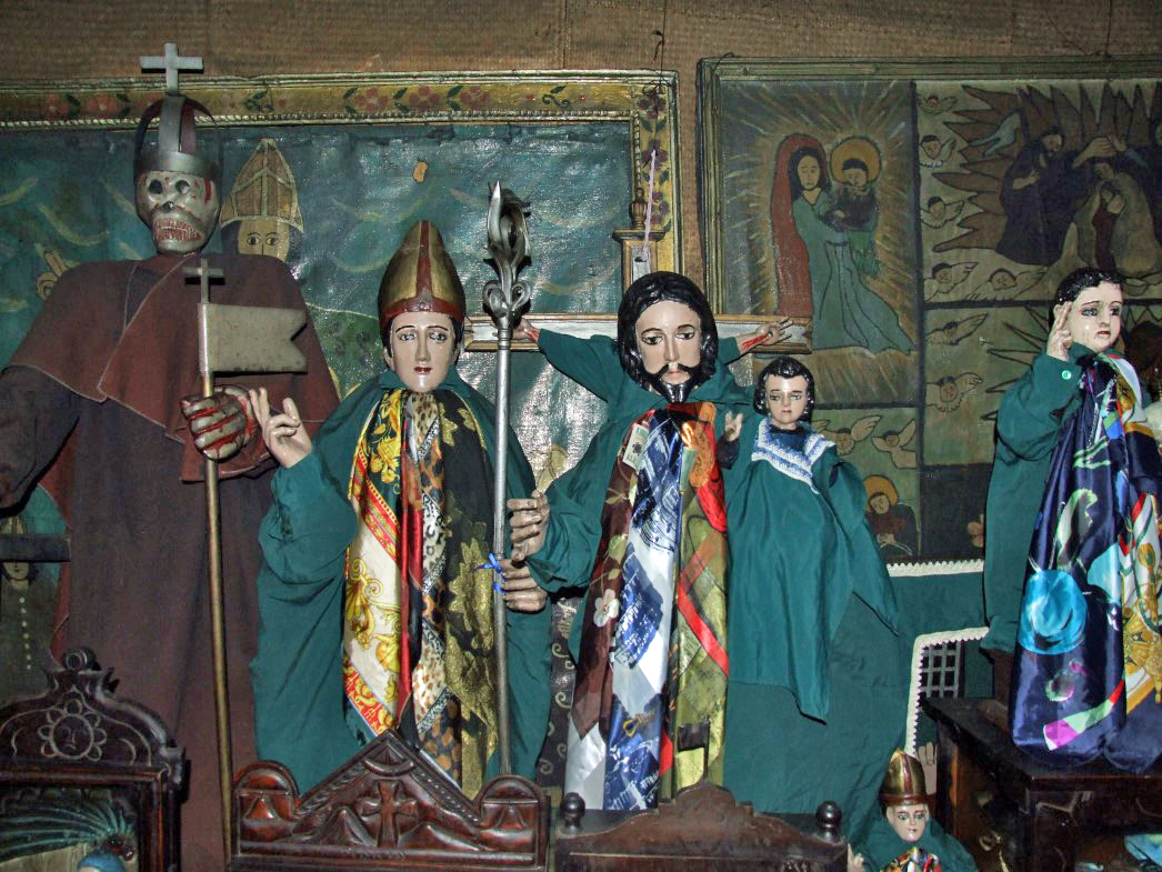 Variety of small saint statues in green clothing