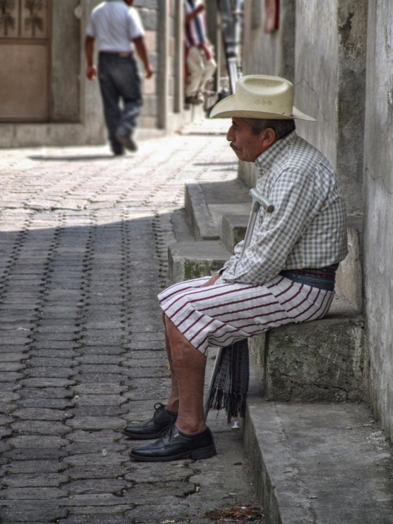 Man sitting in street wearing short striped trousers