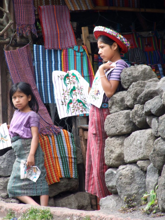 Woman and young girl in traditional dress selling textiles