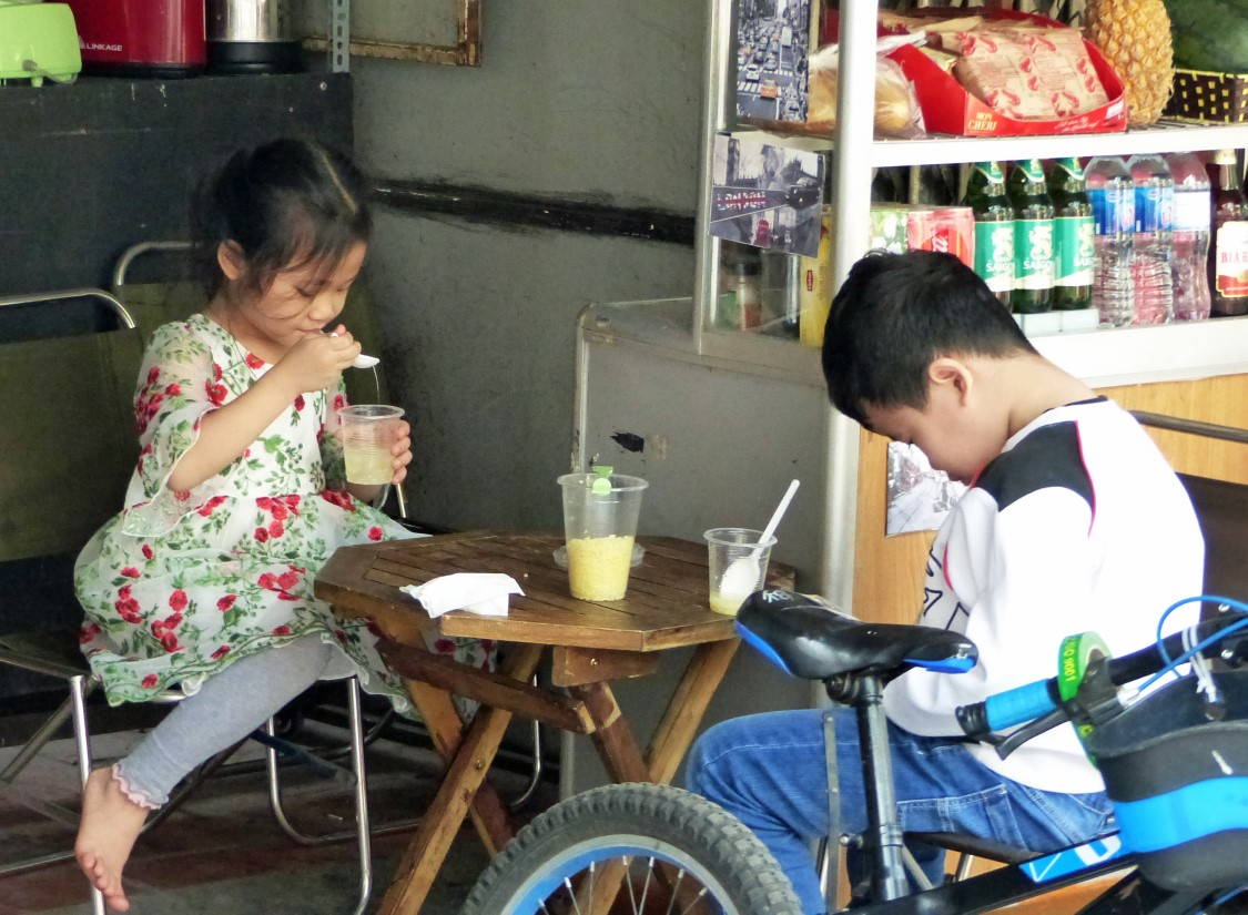 Two children at a low table with lemonade