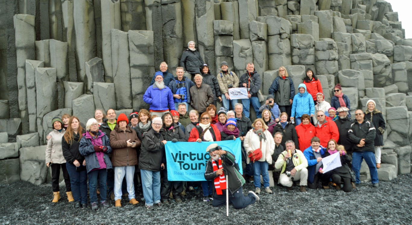 Large group of people in front of a cliff