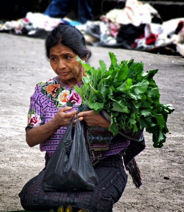 Woman with colourful blouse carrying lettuces