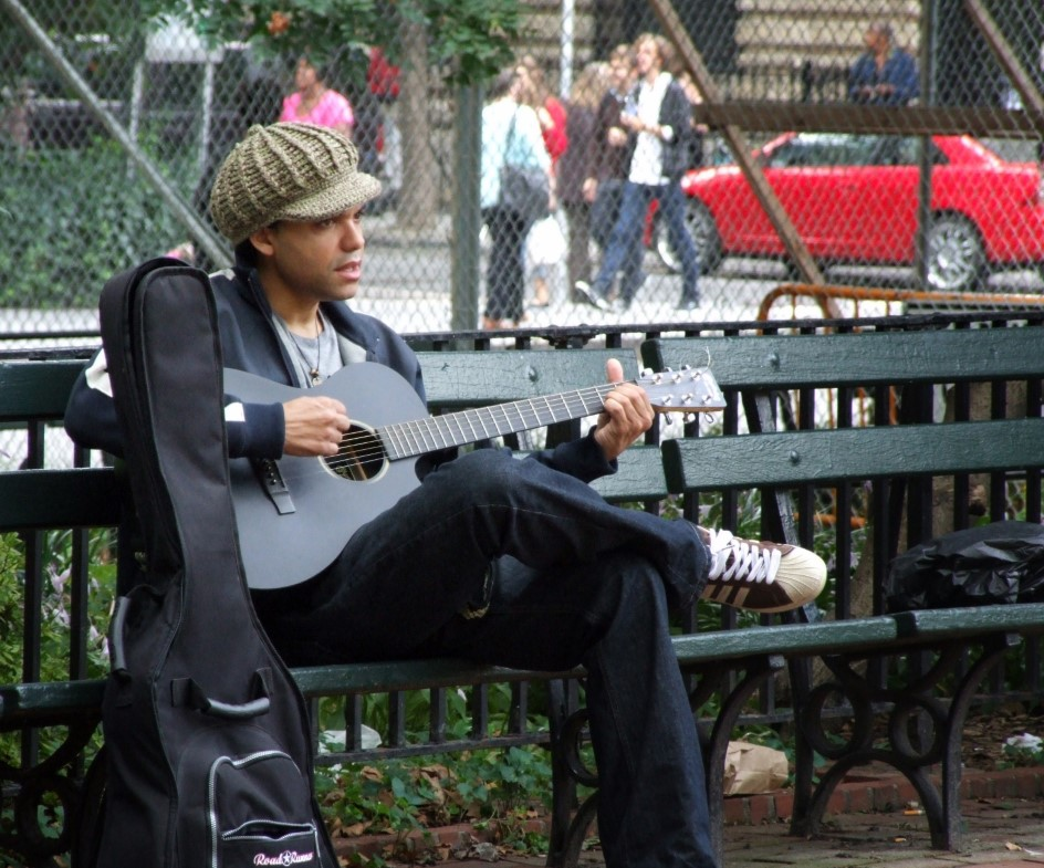 Young man playing guitar on a park bench