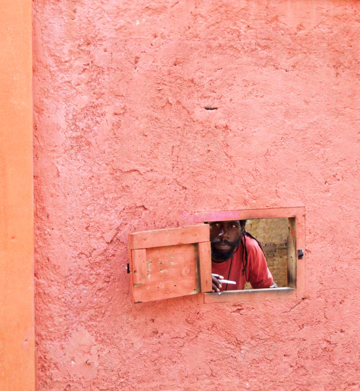Man peering through hole in pink wall