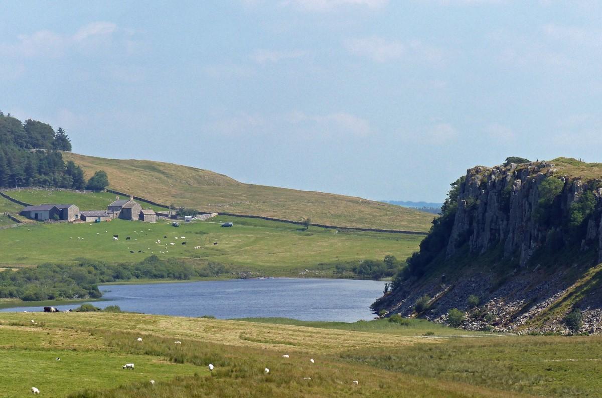 Lake and escarpment with farm beyond