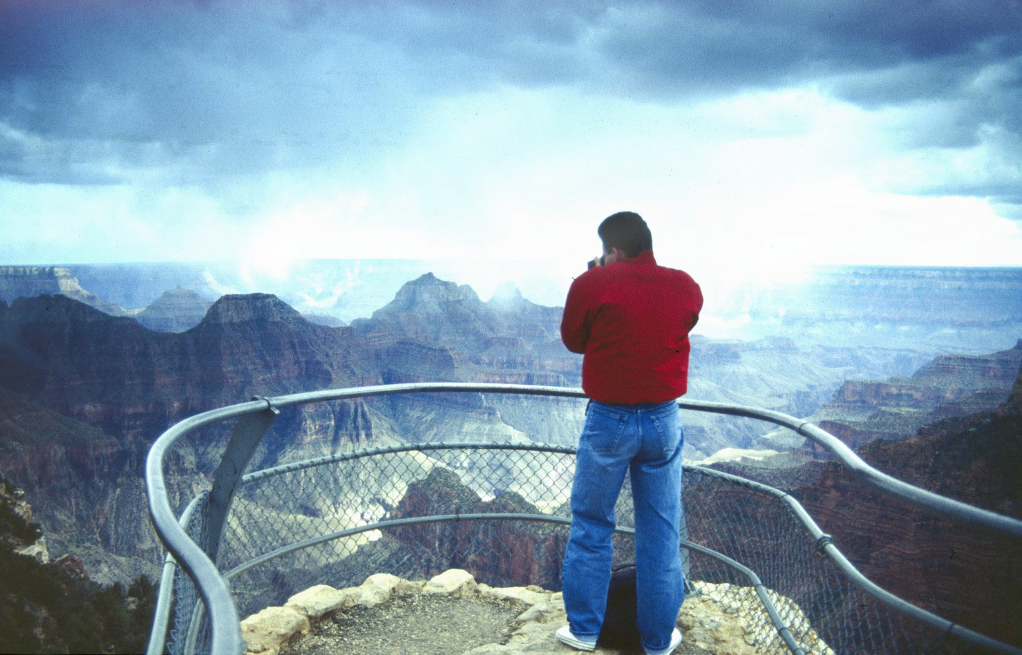 Man in red jacket photographing dramatic landscape