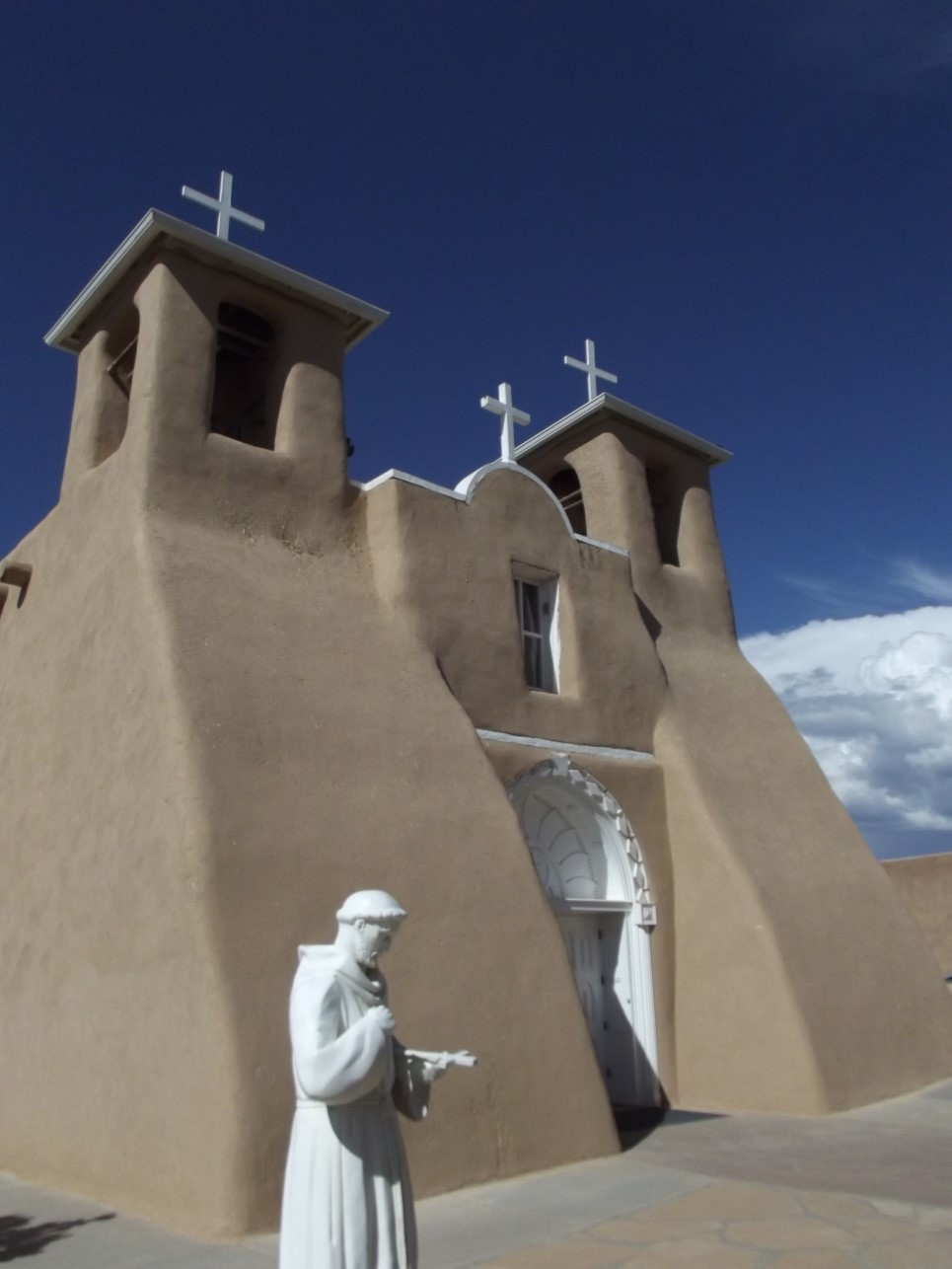 Solid adobe church with white crosses and statue