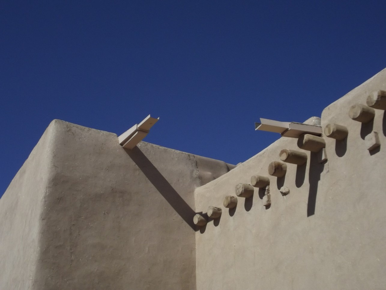 Roof beams sticking out of an adobe building