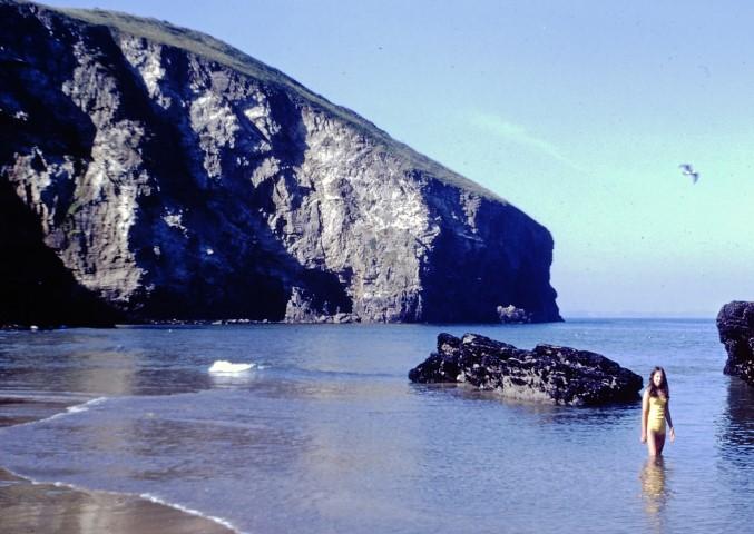 Girl paddling in the sea near cliffs