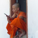 Buddhist monk in orange robes with mobile phone
