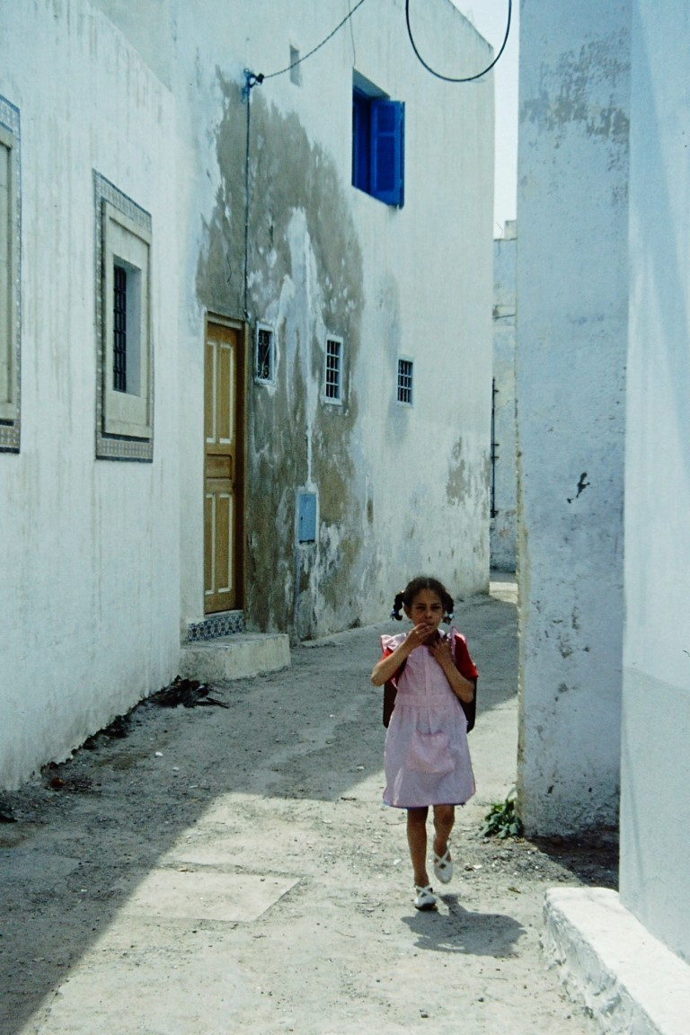 Small girl in a lane line with white houses