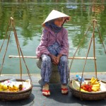 Lady with baskets of fruit sitting by a canal