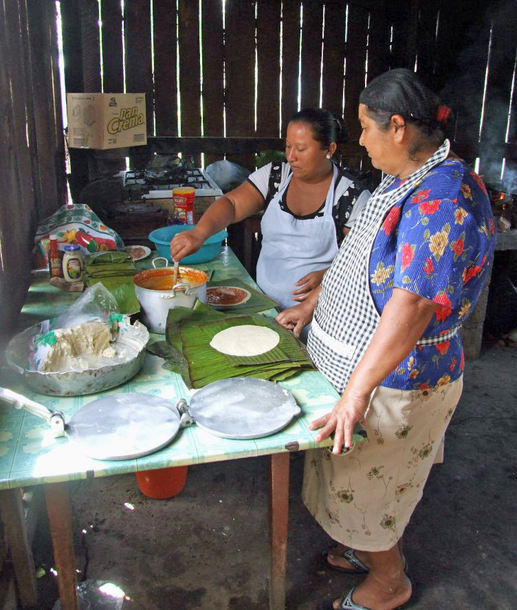 Two women cooking in a wooden hut