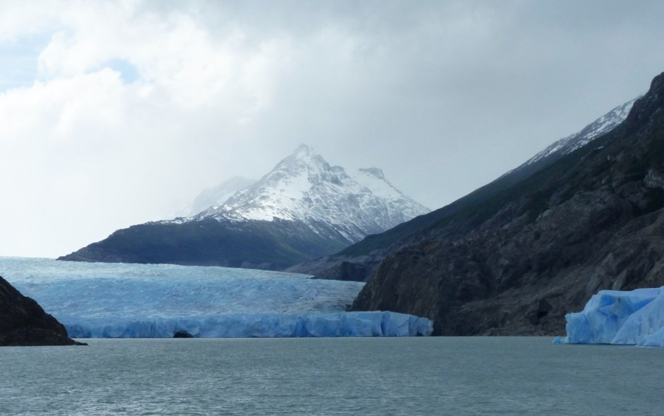 Blue glacier spilling into a lake with mountains beyond