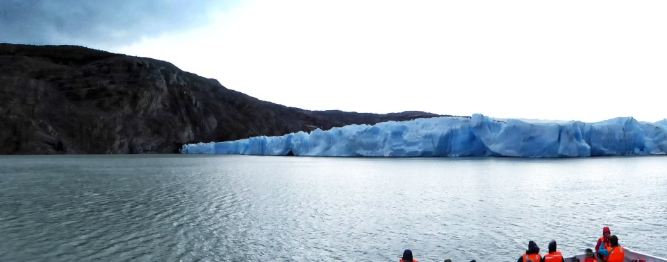 Blue glacier spilling into a lake, seen from a boat
