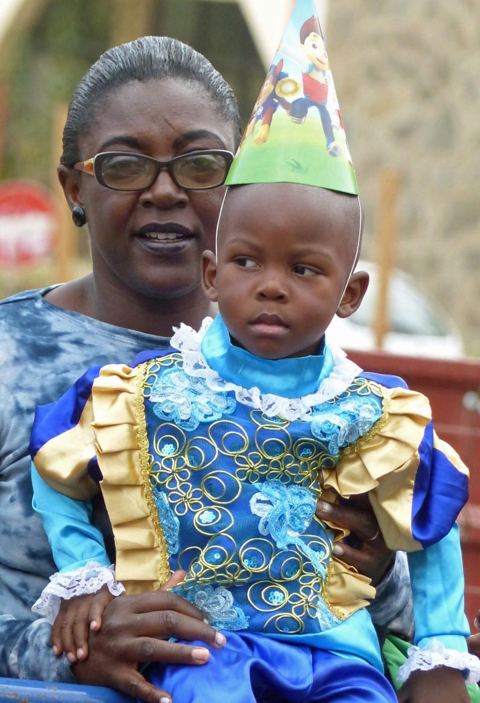 Little boy in fancy dress held by a lady