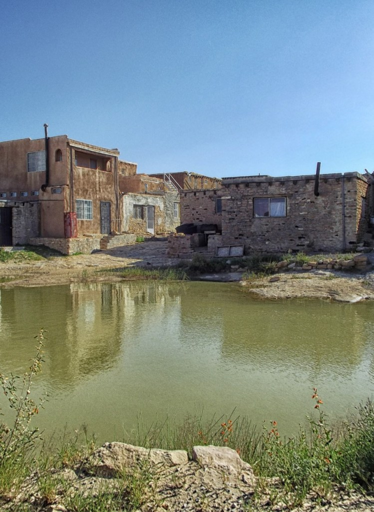 Pool of water with adobe houses beyond