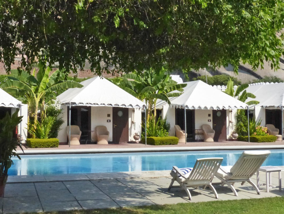 Swimming pool surrounded by trees with small tents