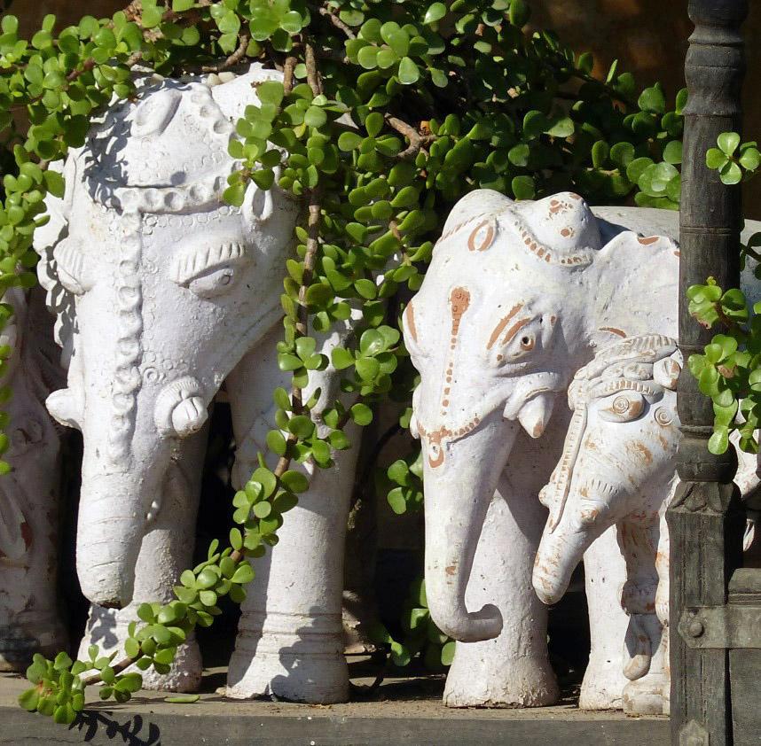 Two stone elephants among greenery