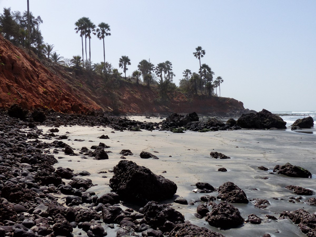 Rocky beach backed by low red cliffs