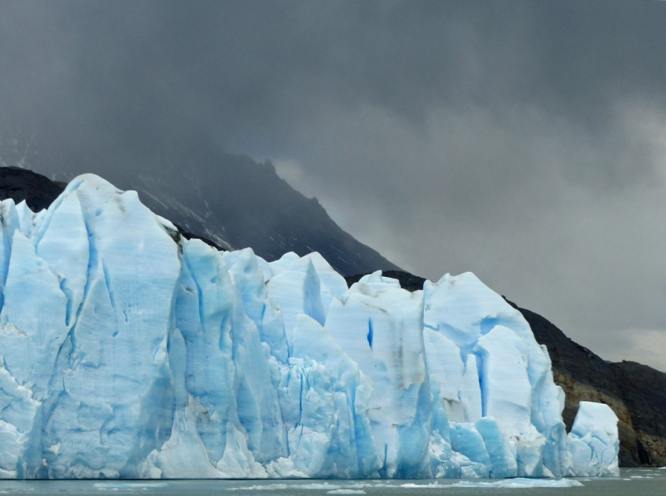 Blue glacier, dark clouds and mountains