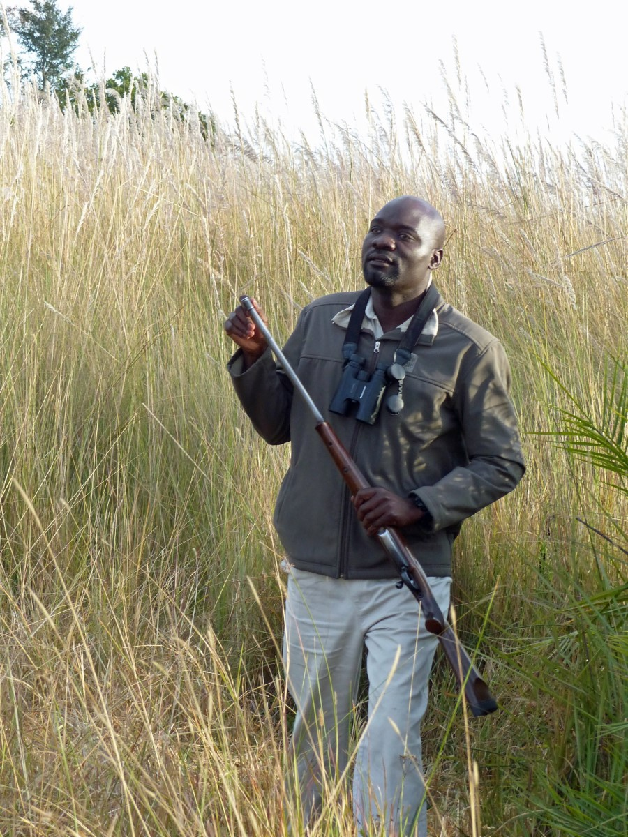 Man in long grass holding rifle