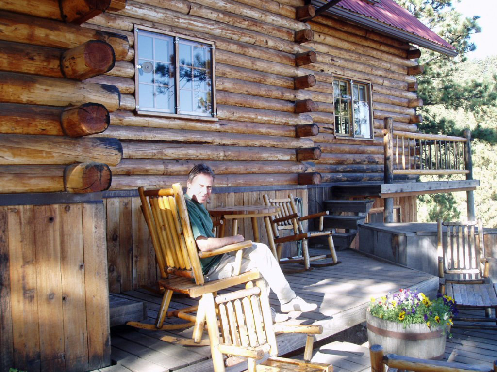 Log house and man sitting on deck