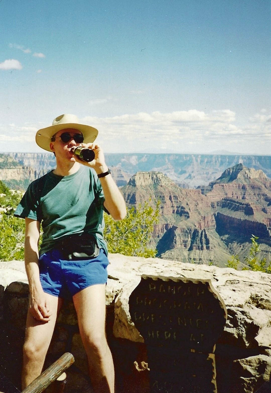 Man drinking beer with canyon landscape behind