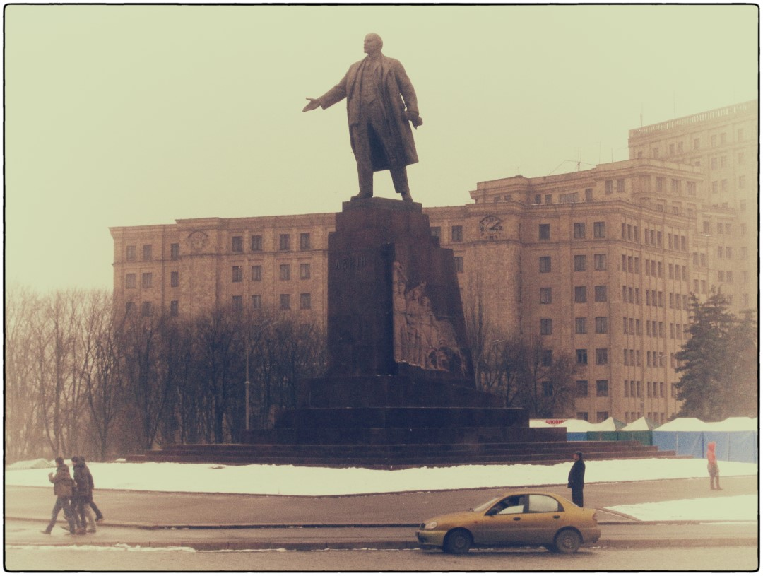 Faded photo of a large statue and old apartments behind