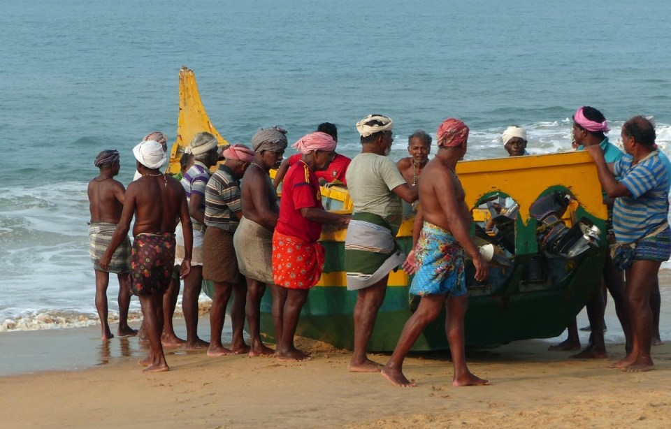 Men in turbans pulling a boat up a beach