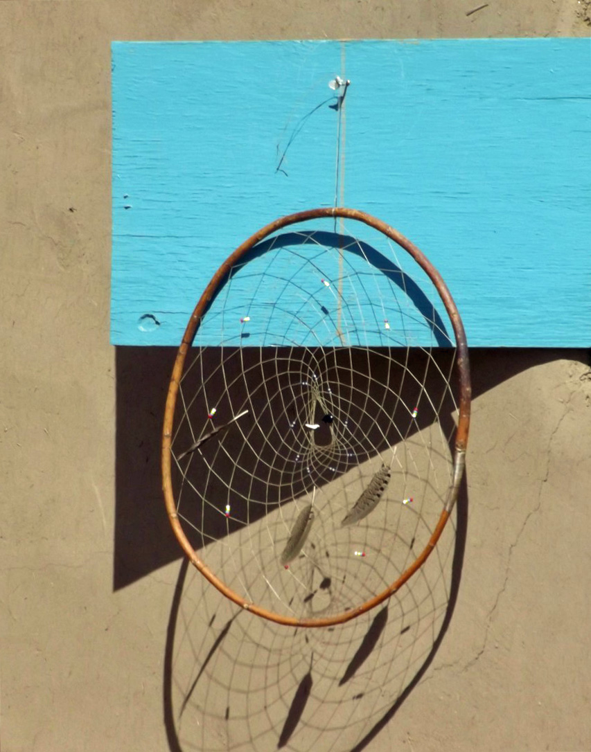 Dream catcher hanging from turquoise plank