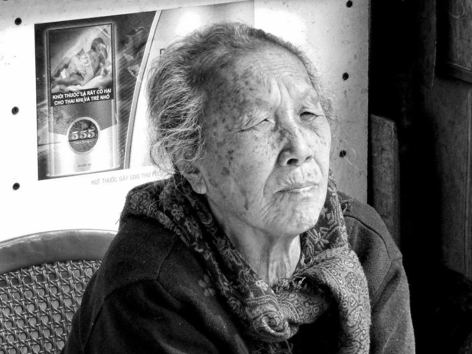 Elderly lady in a basic shop, black and white