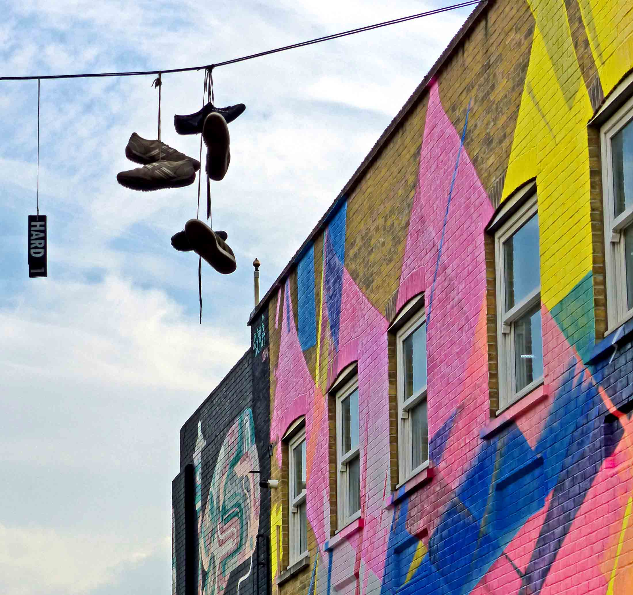 Painted buildings and shoes hanging from telegraph wire