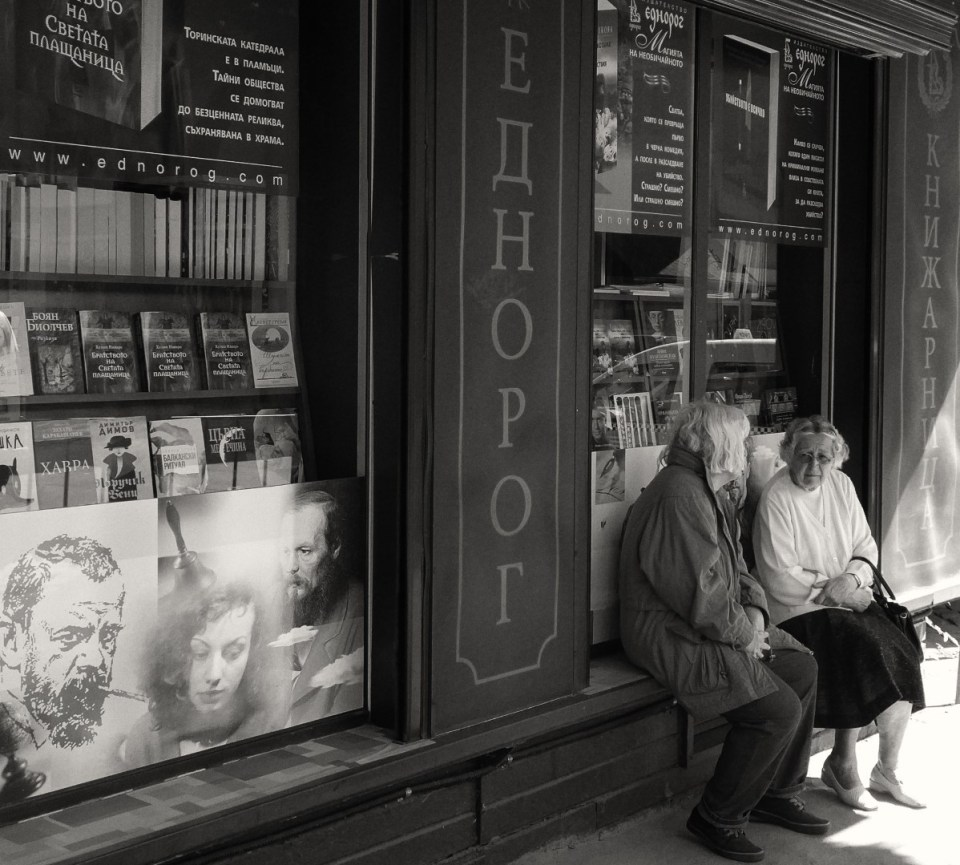 Two ladies sitting outside a shop