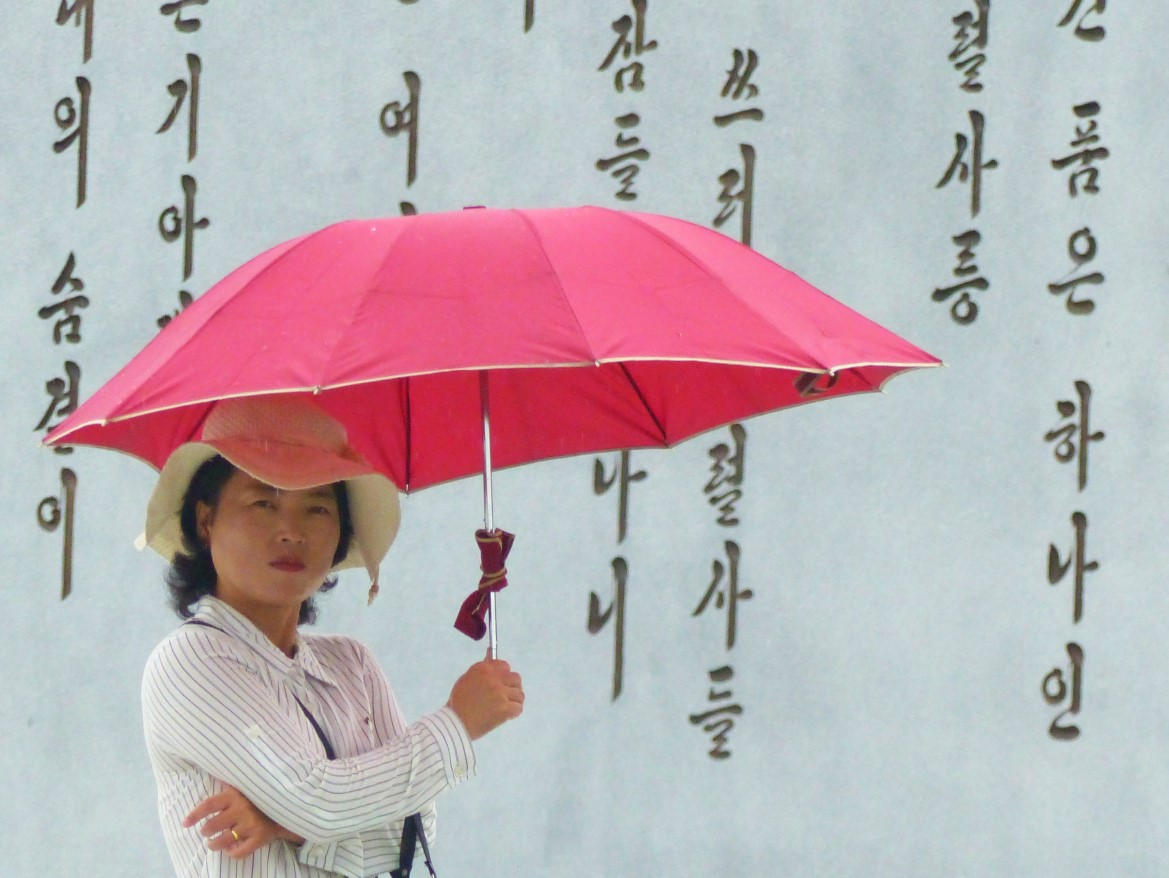 Lady with parasol in front of inscription